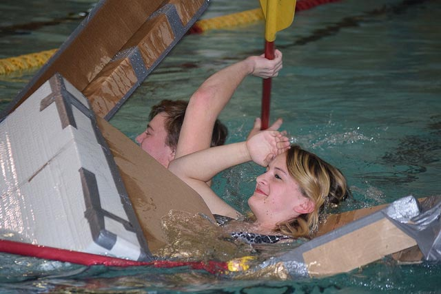 A student gives a farewell salute as her boat sinks during the fall 2016 Mechanical Engineering Learning Team boat design competition