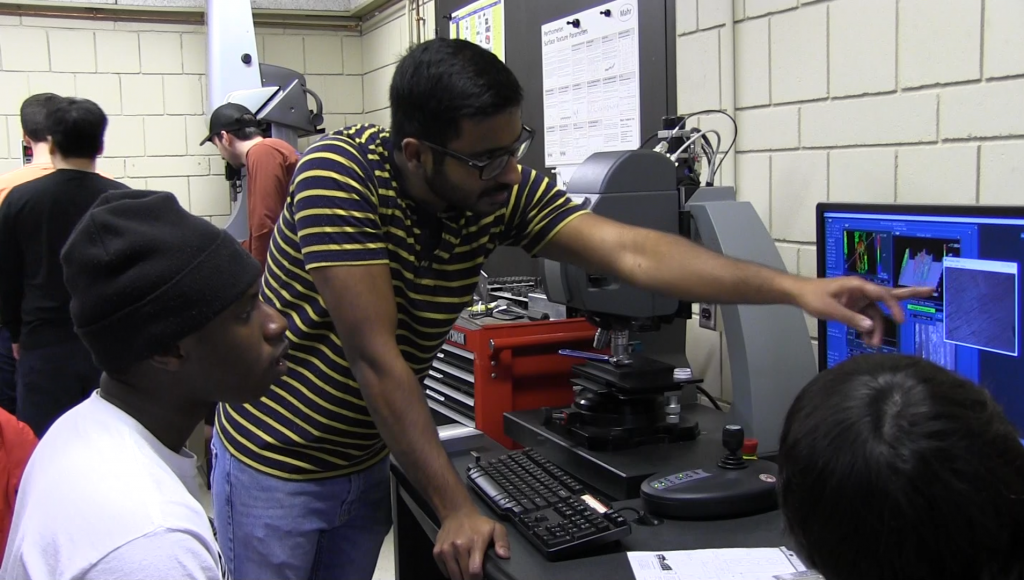 A teaching asssistant works with undergraduate students in the metrology laboratory.