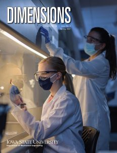 A cover for the Spring 2021 edition of Dimensions, the alumni magazine for mechanical engineering at Iowa State University. In this photo two female students are wearing lab coats, safety glasses, face masks, and rubber gloves. One students examines a 3D-printed sensor under a hood while the other students adjust settings for the hood.